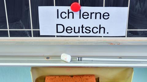 """Zettel mit Aufschrift """"Ich lerne Deutsch"""" an einer Tafel"""