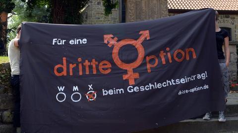 Menschen halten Banner für Wahl des dritten Geschlechts im Pass hoch