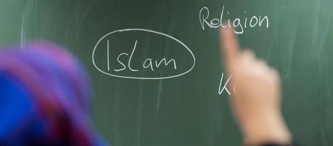 Eine Schülerin mit Kopftuch meldet sich an einer Schule in Frankfurt bei einer Unterrichtsstunde zum Thema Islam.