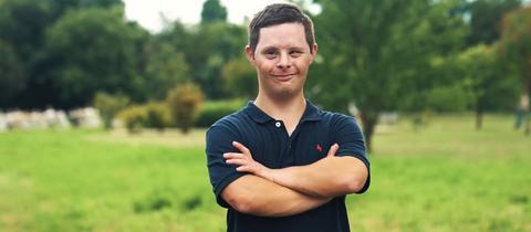 Jan steht mit verschränkten Armen in einer Landschaft und lächelt in die Kamera.