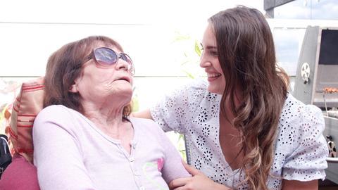 Seniorin in Rollstuhl und Enkelin lächeln sich gegenseitig an