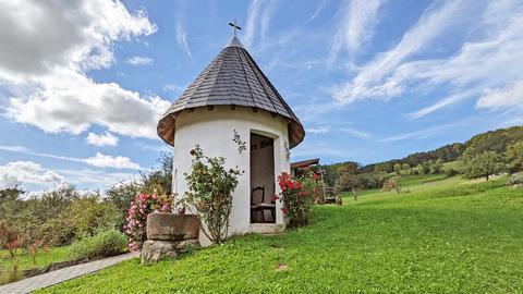 Ein kleines rundes Gebäude mit rundem Spitzdach und offener Tür steht auf einer Wiese.