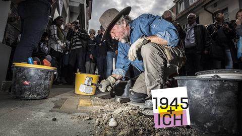 Das Foto zeigt den Künstler Gunter Demnig wie er Stolpersteine in einer hessischen Stadt verlegt.