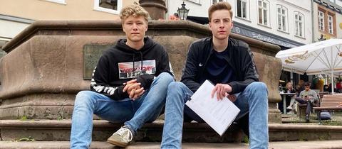 Jonathan Faust und Tom Kelwald sitzen an einem Brunnen auf der Treppe. XY hält die Klageschrift in seiner Hand. Beide tragen Jeans, Turnschuhe und dunkle Oberteile.