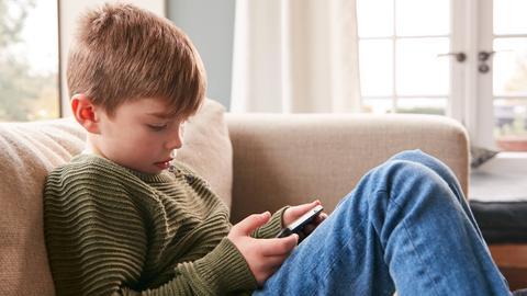 Junge sitzt deprimiert mit dem Handy auf einem Sofa