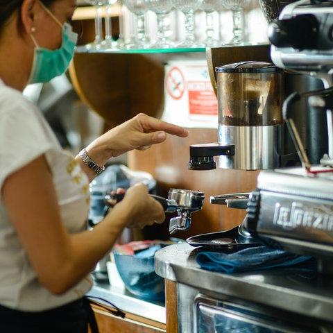 Eine Barista steht an einer Espressomaschine und bereitet einen Milchkaffee.