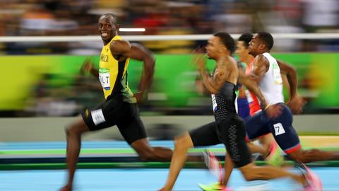 Sprinter Usain Bolt blickt kurz vor Zieleinlauf auf die Konkurrenz zurück