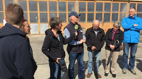 Ein Stadtführer steht mit einer Gruppe vor einem Gebäude in Gießen und wird von einer hr-Reporterin interviewt