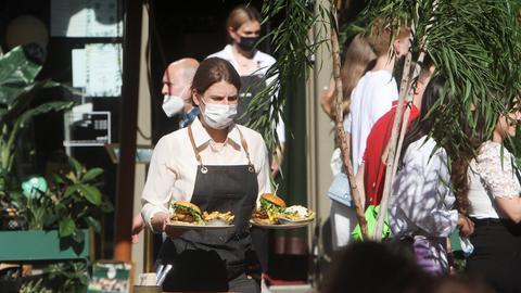 Szene in einer Außengastronomie. Eine Kellnerin mit OP-Maske trägt zwei Teller mit Burgern zu einem Tisch.