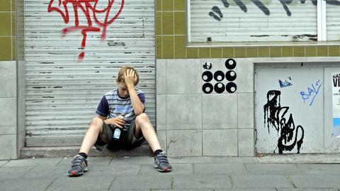 Junge sitzt vor geschlossenem Laden