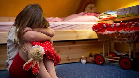 Ein Mädchen sitzt zusammengekauert in einem Kinderzimmer.