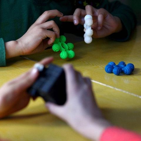 Kinderhände, die Spielzeuge zur Förderung der Konzentation in den Händen halten.
