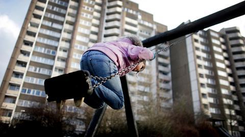Ein Mädchen schaukelt vor tristen Wohnblocks