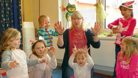 Erzieherin mit einer Gruppe von Kindern beim Spielen