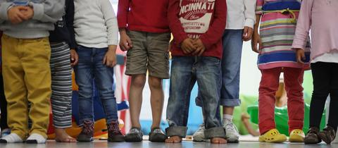 Kindergartenkinder stehen in einer Reihe eng zusammen