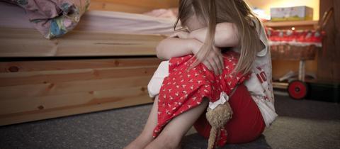 Kind sitzt auf dem Boden und vergräbt seinen Kopf zwischen den Armen