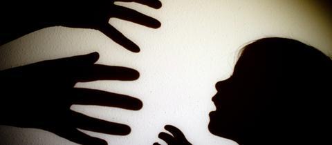 Zwei Hände greifen als Schatten nach einem Kind