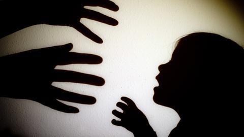 Schatten von Händen einer erwachsenen Person und der Kopf eines Kindes an einer Wand eines Zimmers
