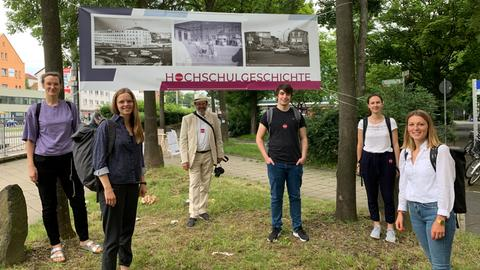 Studierende stehen vor einem Plakat. Es zeigt historische Aufnahmen vom Uni-Standort am Holländischen Platz.