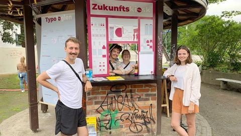 """Vier Studierende, zwei Frauen und zwei Männer stehen vor dem temporär eingerichteten Kiosk an der Goetheanlage in Kassel. Auf große Plakaten haben sie """"Zukunfts-Kiosk"""" geschrieben und den Kiosk damit eingerichtet."""