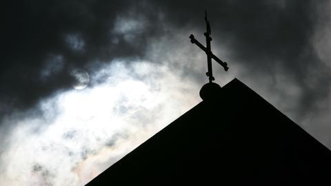 Kreuz auf Kirchendach unter bewölktem Himmel