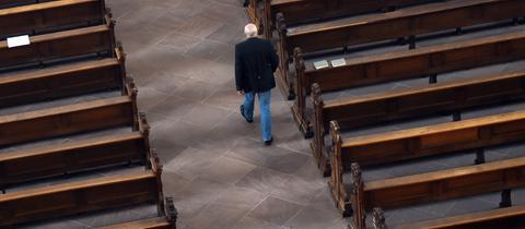 Mann läuft durch leere Kirche