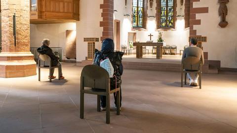 Weit voneinander entfernt sitzen Menschen in der Alten Nicolaikirche am Frankfurter Römerberg. Hier sollen bald wieder Gottesdienste stattfinden.