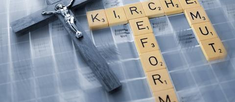 Ein Kreuz und Scrabble-Buchstaben mit den Worten Kirche, Reform und Demut.