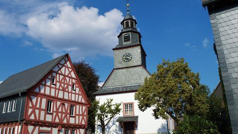 Ein rot-weiß gestrichenes Fachwerkhaus neben einer Kirche