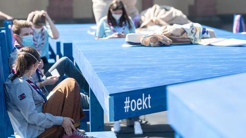 """Pfadfinder sitzen am ersten Tag des 3. ökumenischen Kirchentags auf der Installation """"Ein Tisch"""" auf der Frankfurdter Hauptwache. Sie ist einer der wenigen sichtbaren Repräsentanten des größtenteils digital stattfindenden Kirchentags."""