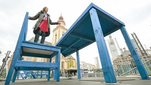 Eine Frau steht auf einem überdimensionalen Stuhl, welcher an einem überdimensionalen Tisch platziert ist. Das Ensemble ist von unten fotografiert, so dass neben der Frau der ein Kirchturm und die Spitzen einiger Hochhäuser zu sehen sind.