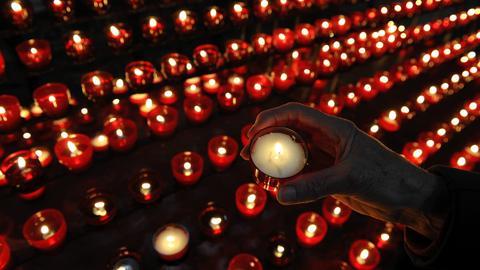 Dutzende kleine Kerzen leuchten in der Dunkelheit.