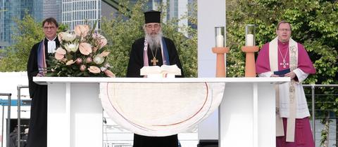 """Drei Geistliche stehen an einem """"Outdoor-Altar"""" und halten Abschlussgottesdienst. Der Altar ist geschmückt mit Blumen, der heiligen Schrift und Kerzen."""