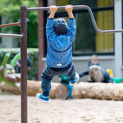 Ein kleines Kind hängt an einer Stange auf dem Spielplatz und lässt sich pendeln.