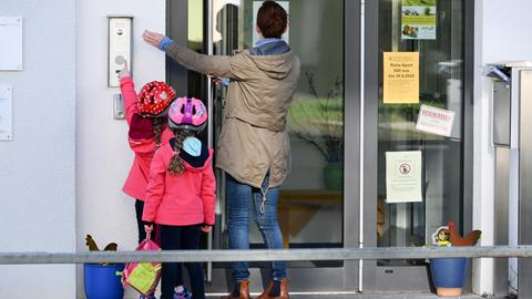 Mutter mit Kindern klingelt an der Kita-Tür