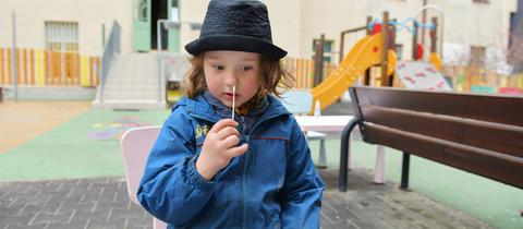 Ein Kind testet sich selbst auf das Coronavirus.