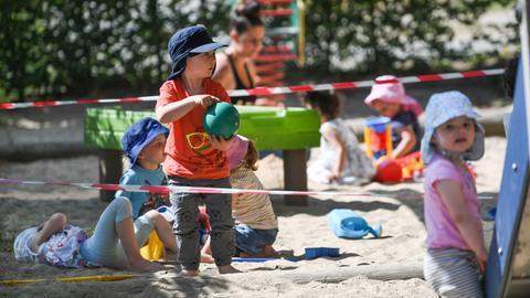 """Kinder der Krippen-Gruppe """"Regenbogenfische"""" spielen auf dem Spielplatz der Kita am Offenbacher Sana Klinikum, auf dem Absperrbänder den Abstand zu den Gruppen markieren."""