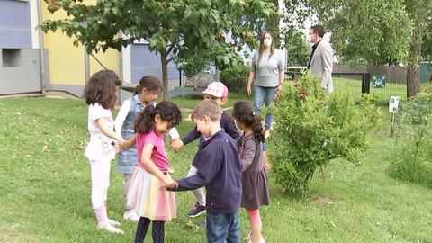 Foto von spielenden Kindern im Garten des AWO Kita Familienzentrums in der Marshallstraße. Im Hintergrund eine Erzieherin und ein Erzieher.