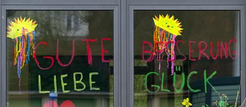 """""""Gute Besserung - Liebe Glück"""" steht an einem Kita-Fenster in Kassel."""
