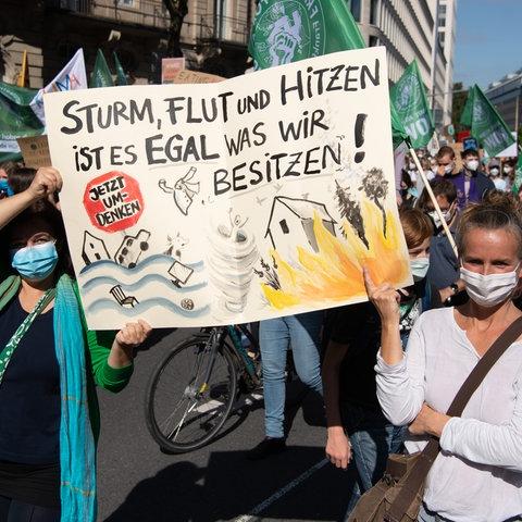 """Zwei Demonstrantinnen halten ein Plakat hoch, auf dem steht: """"Sturm, Flut und Hitzen ist es egal, was wir besitzen."""""""
