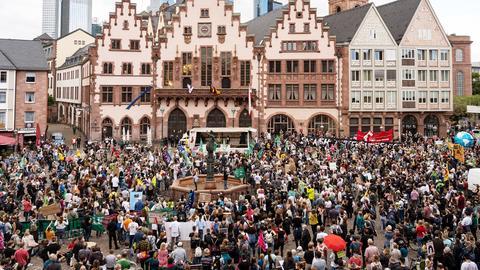 Eine Menschenmenge, teilweise mit Plakaten und Fahnen in den Händen, befindet sich vor dem Frankfurter Rathaus
