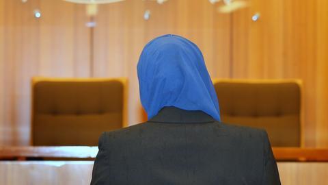 Klagende Jurastudentin vor Gericht - eine Frau von hinten mit blauem Kopftuch.
