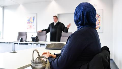 Eine Frau mit Kopftuch vor einem Anwalt.