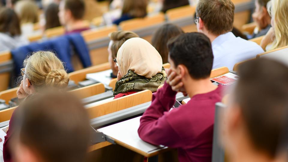 Eine Studentin sitzt mit Kopftuch in einem Hörsaal.