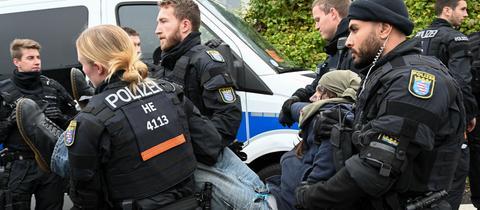 Polizisten tragen einen Demonstranten weg.