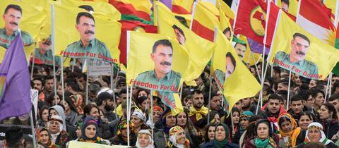 Kurdische Demonstranten während der Kundgebung zum kurdischen Frühjahrsfest Newroz in Frankfurt mit Fahnen mit dem Logo und dem Konterfei des PKK-Führers Öcalan.
