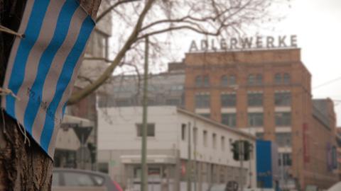 Stoffbinde um einen Baumstamm vor den ehemaligen Adlerwerken in Frankfurt zur Erinnerung an das KZ dort