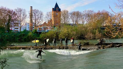 Eine Fotomontage der Stadt Gießen mit einer Surferwelle, auf der Menschen surfen