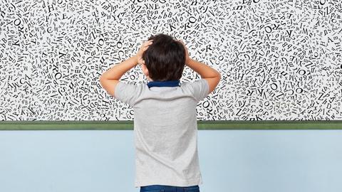 Junge vor einem Whiteboard mit vielen Buchstaben durcheinandergewürfelt