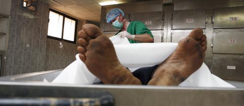 Ein Rechtsmediziner begutachtet eine Leiche